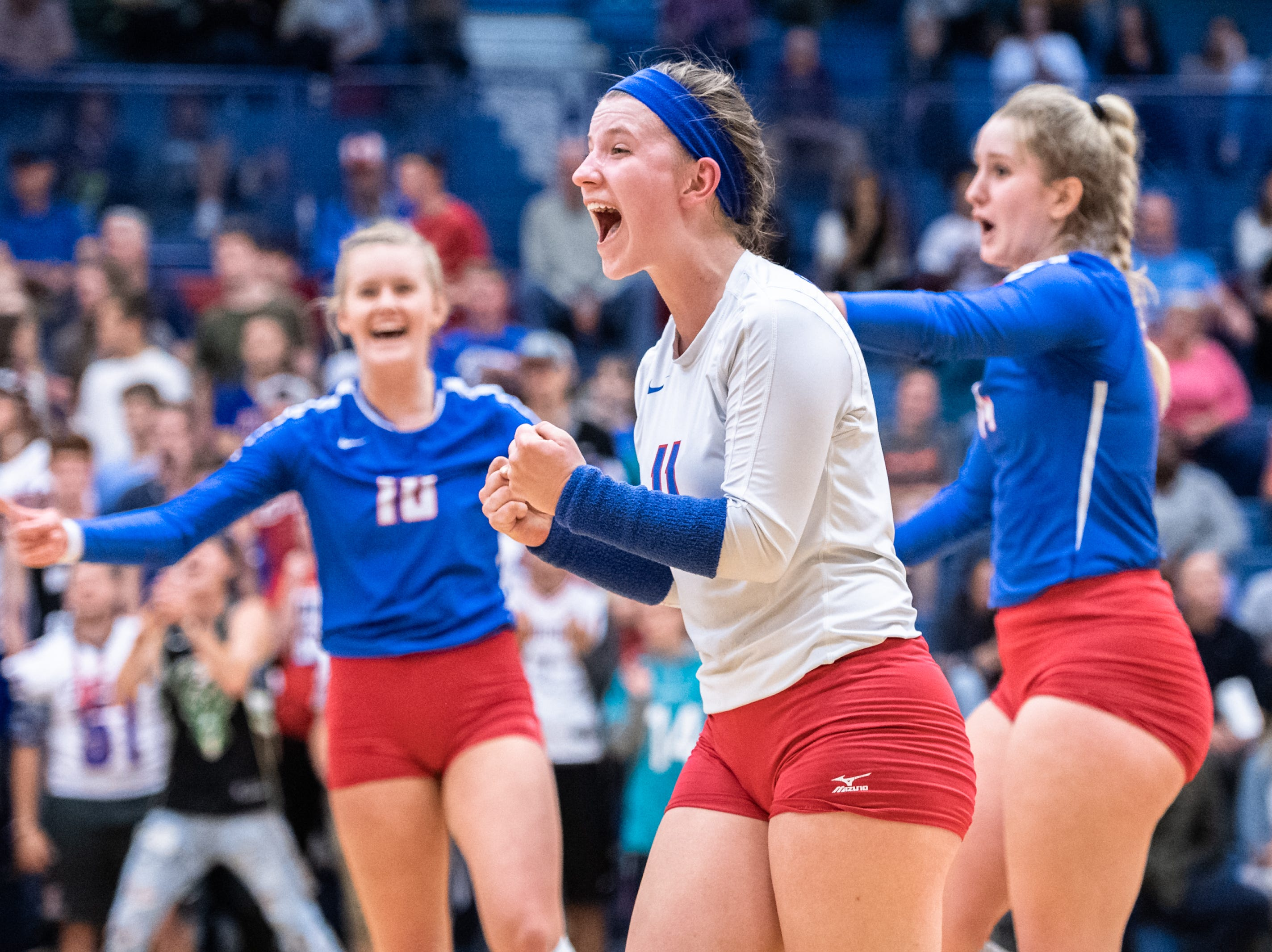 West Henderson's Ashley Downer reacts with Malia Moore and Casey Brown to a point scored during their WMAC tournament championship volleyball game against Reynolds Oct. 18, 2018.