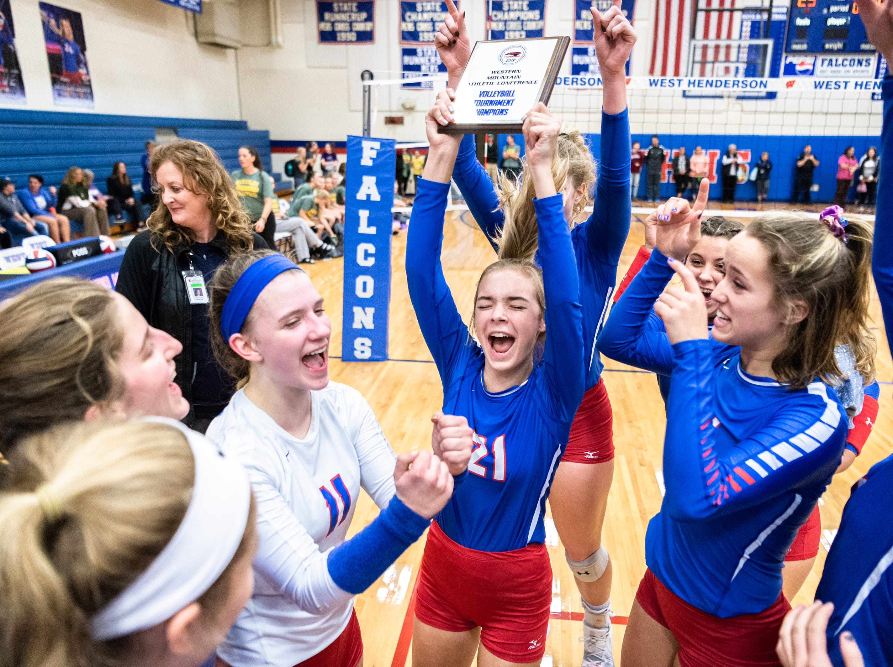 The West Henderson volleyball team celebrates defeating Reynolds in their WMAC tournament championship volleyball game Oct. 18, 2018.
