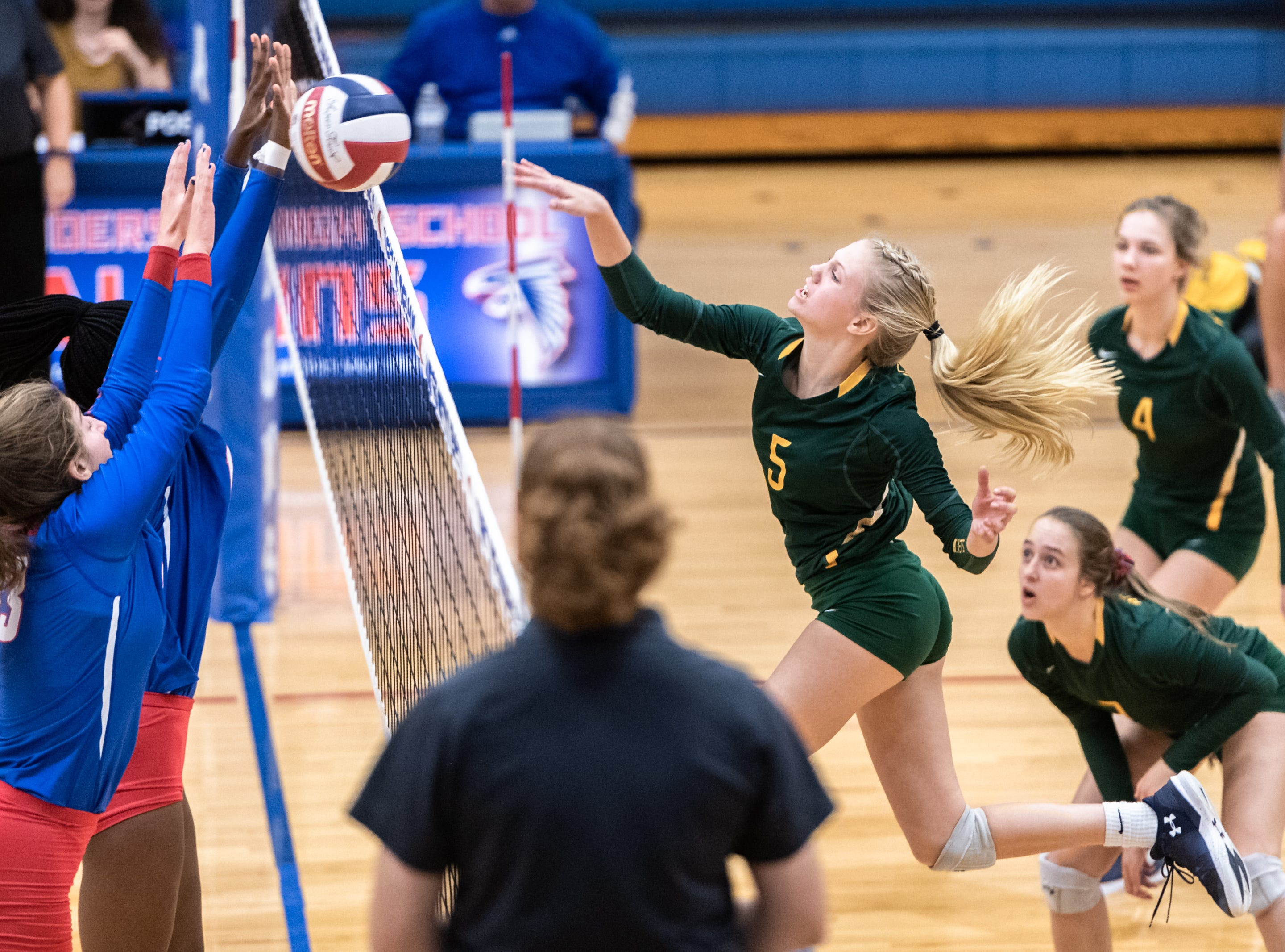 West Henderson's Daija Jackson and Darby Fisher block a shot by Reynolds' Abby Hutzler during their WMAC tournament championship volleyball game Oct. 18, 2018.