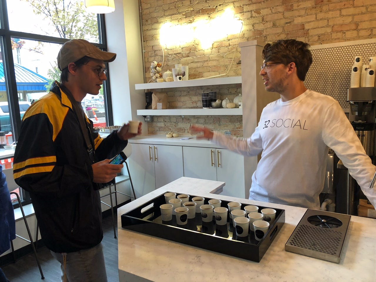 Caleb Minear, left, talks to his brother Jake Minear at 32 Social. The coffee shop had samples Friday night during Fall into the Arts and looks to open soon.