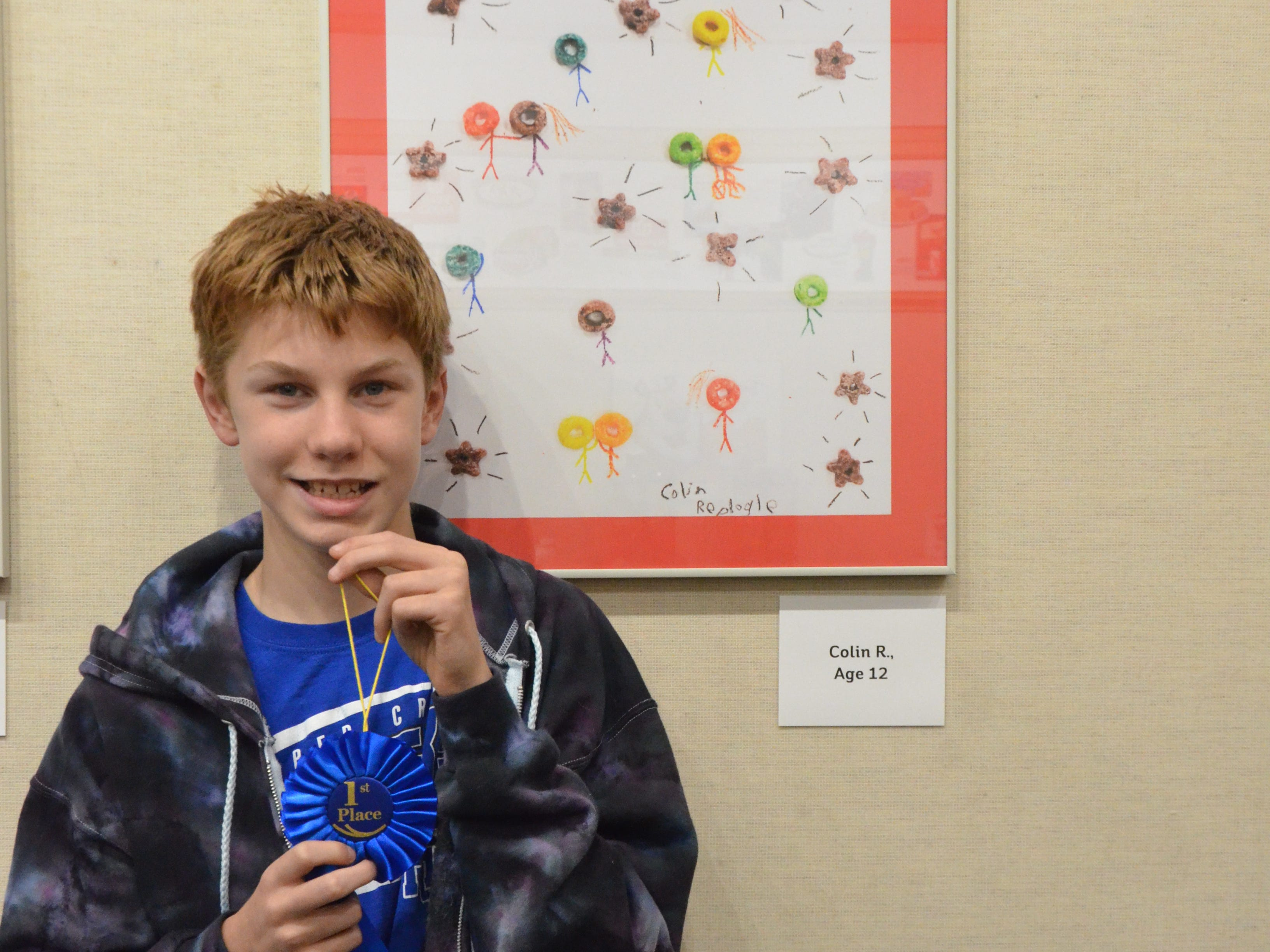 "Colin Replogle stands in front of his Froot Loops art, which he described as friends hanging out together, at Kellogg World Headquarters on Friday Night. Kellogg participated in Fall into the Arts with student winners from their ""Whatever Froots Your Loops"" anti-bullying program."