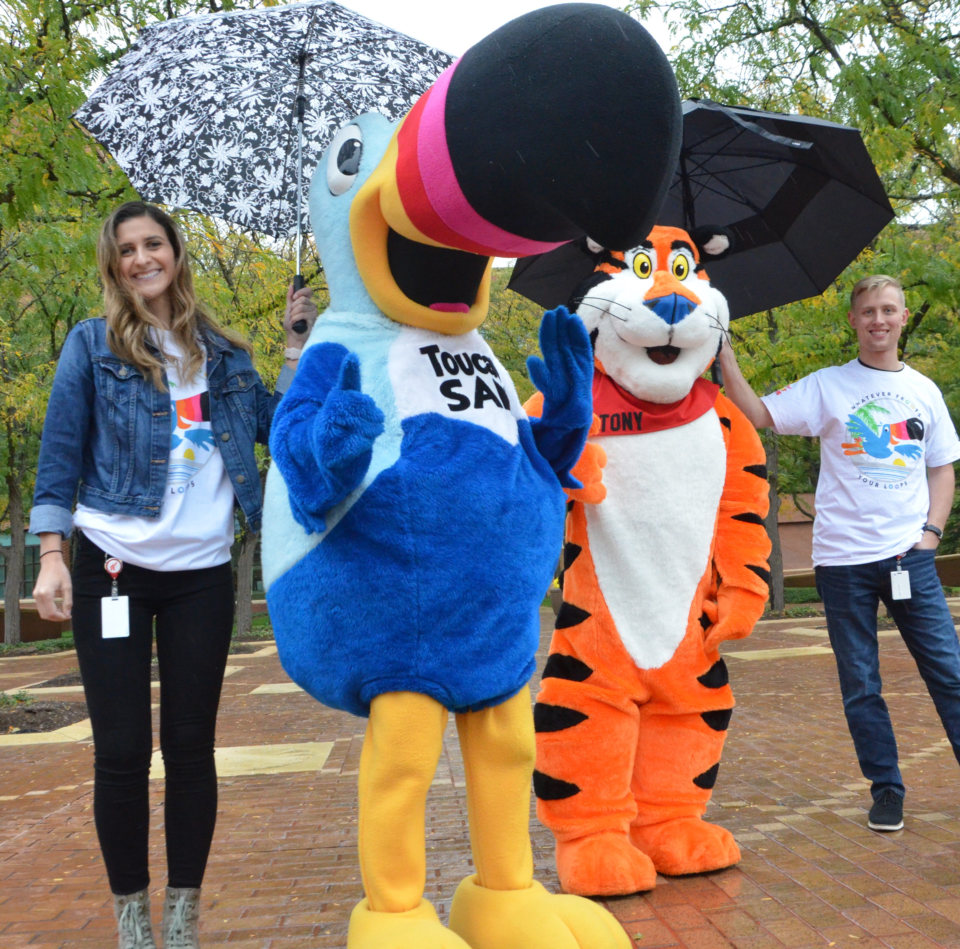 Toucan Sam and Tony the Tiger greeted guests in front of Kellogg World headquarters for Fall into the Arts. Helping to keep them dry was Michaela Gilmore, left, and Anthony Brenner.