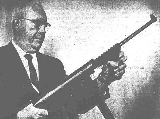 Detective Raymond Martin holds a semi-automatic weapon seized during an arrest at the Mate's Club.