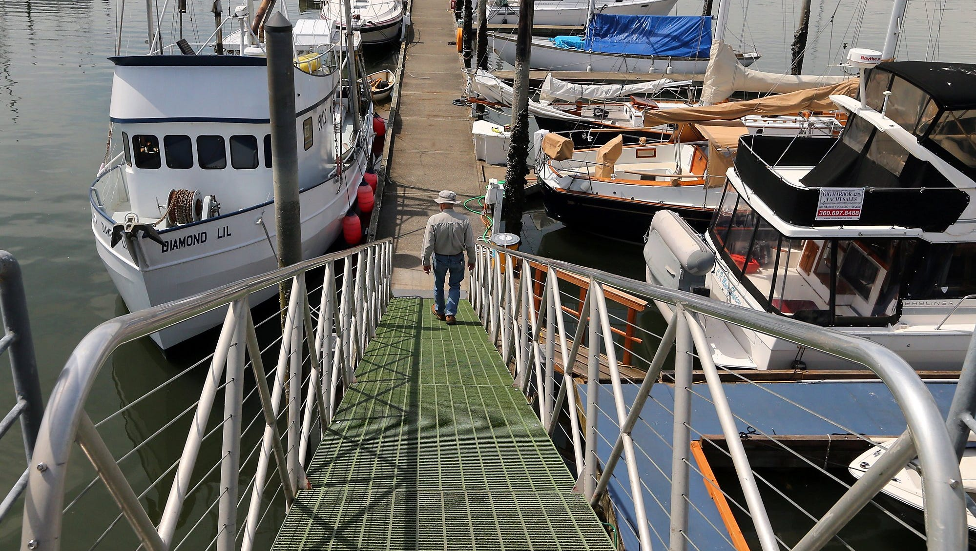 2015 FILEA boater walks down the steep dock during low tide at the Poulsbo Marina on Thursday, May 21, 2015.