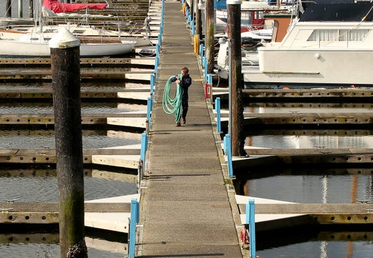 2016 FILEPort of Poulsbo dock hand Sam Hughes carries a coiled hose down the dock after spraying off the Guest Moorage docks at the marina on Tuesday, March 22, 2016.