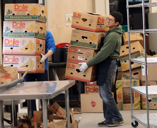 Matthew Menezes, a missionary with Church of Jesus Christ of Latter-day Saints from Brazil, carries empty fruit boxes out of the North Kitsap Fishline while volunteering on Friday, October 19, 2018.