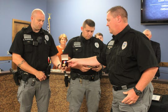 Black Mountain police chief Shawn Freeman presents life-saving medals to officers Jon McDonald and Ian Ammons as the mayor and board of aldermen look on during their Oct. 8 meeting.