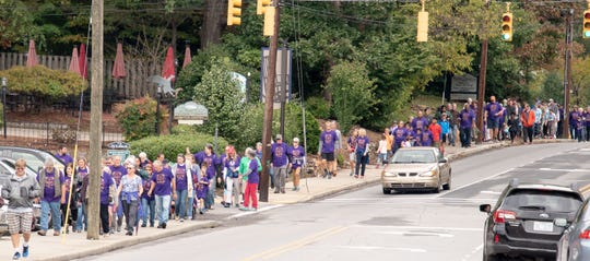 Hundreds of people wearing purple shirts walk along State Street in Black Mountain in the 2018 Walk for Hunger Relief. The event, which supports the food pantry at Swannanoa Valley Christian Ministry, will return on Oct. 13.