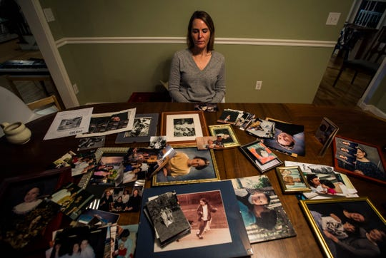 Kate O'Neill, sister of Madelyn Ellen Linsenmeir who died after a 14-year battle with opioid addiction, looks over a lifetime of family photos. O'Neill wrote an obituary that candidly described how opioids destroyed her sister's life which gained national attention.