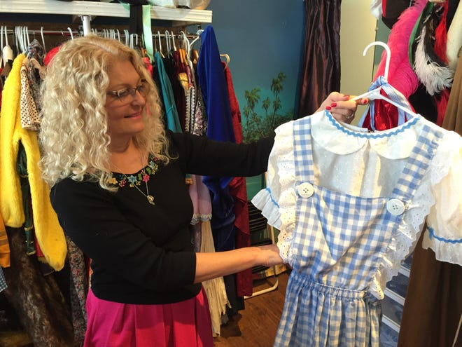 """Laurie Browne, owner of the Triple Loop Costume Shop in Essex Junction, holds a costume representing Dorothy from """"The Wizard of Oz."""""""