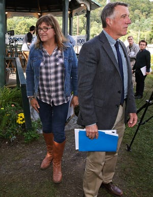 Vermont Republican incumbent Gov. Phil Scott, right, and Democratic challenger Christine Hallquist, center, walk from a gazebo following a debate at the Tunbridge World's Fair in Tunbridge, Vt.