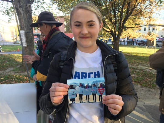 Burlington High School senior Elizabeth McConnell, 18, holds a photo outside a talk on Oct. 19, 2018, from a student walkout she led after becoming inspired last winter by the Parkland High School student founders of the March for Our Lives movement.