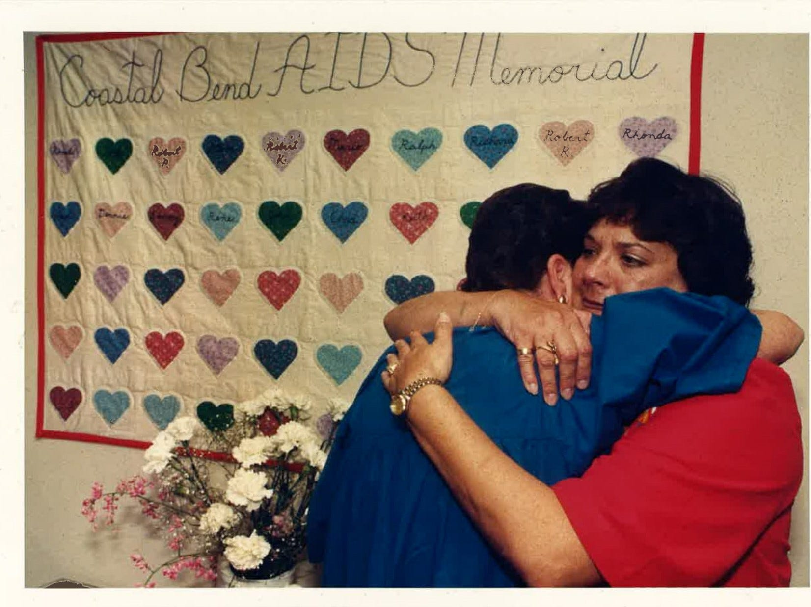 Judy Hale hugs Lisa Franke in front of the Coastal Bend Aids Memorial Quilt at the Coastal Bend Aids Foundation, which is now the Coastal Bend Wellness Foundation. The picture was published in the Caller-Times on August 19, 1988