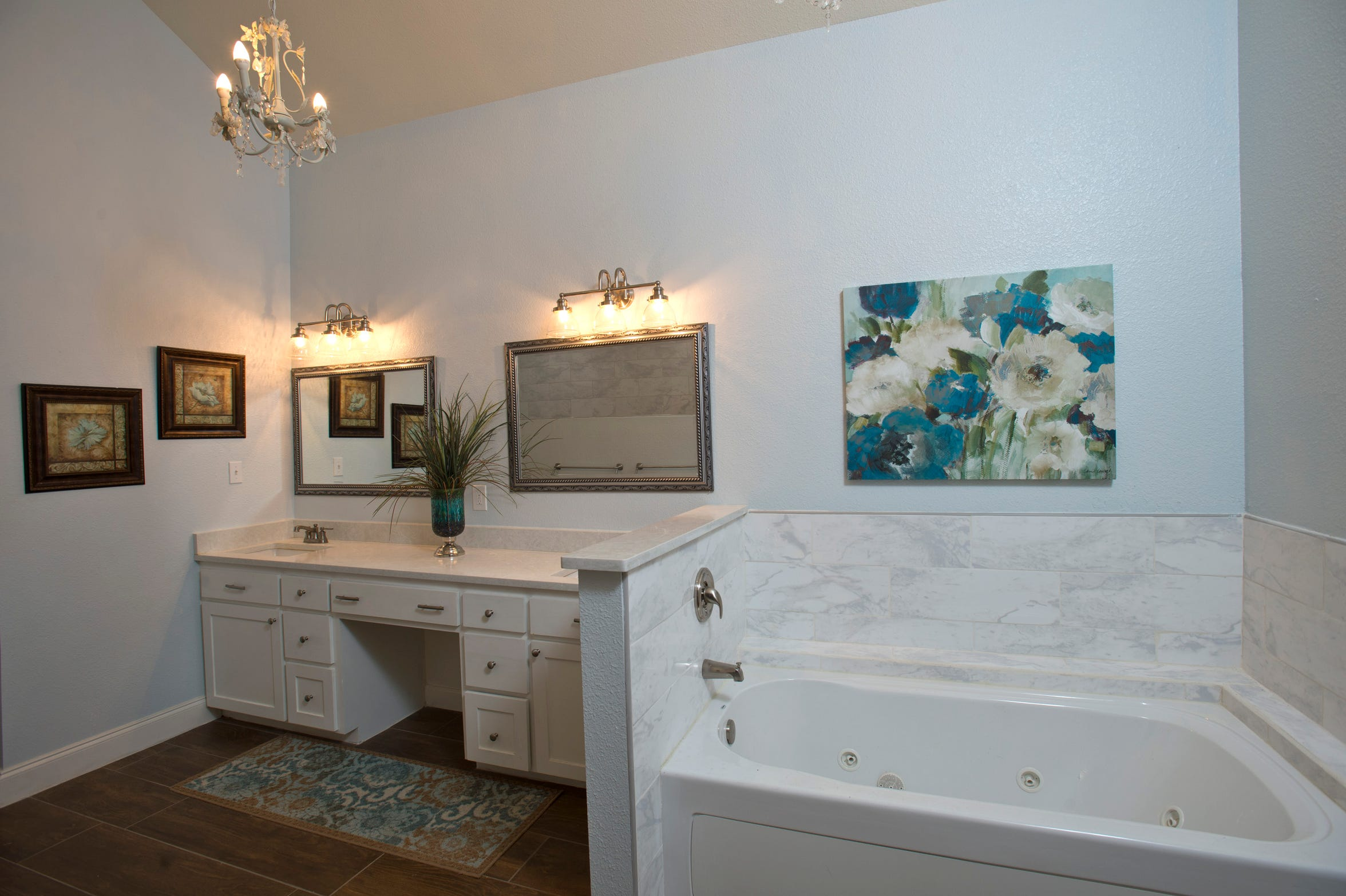 The master bath has a vaulted ceiling, whirlpool tub, wood look tile flooring plus a huge walk in shower