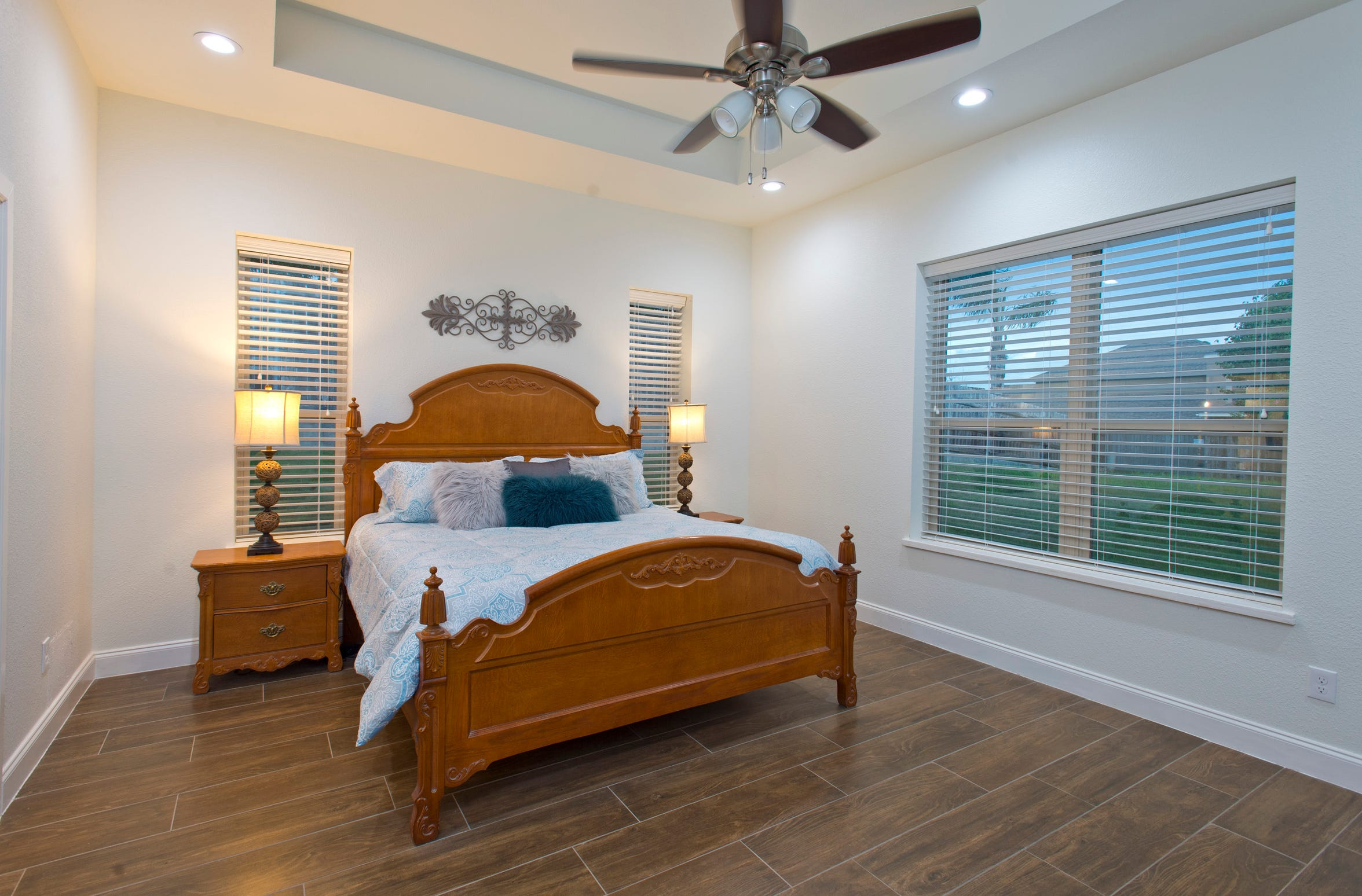 The master bedroom features a recessed ceiling, wood look tile folding and lots of window area overlooking the yard
