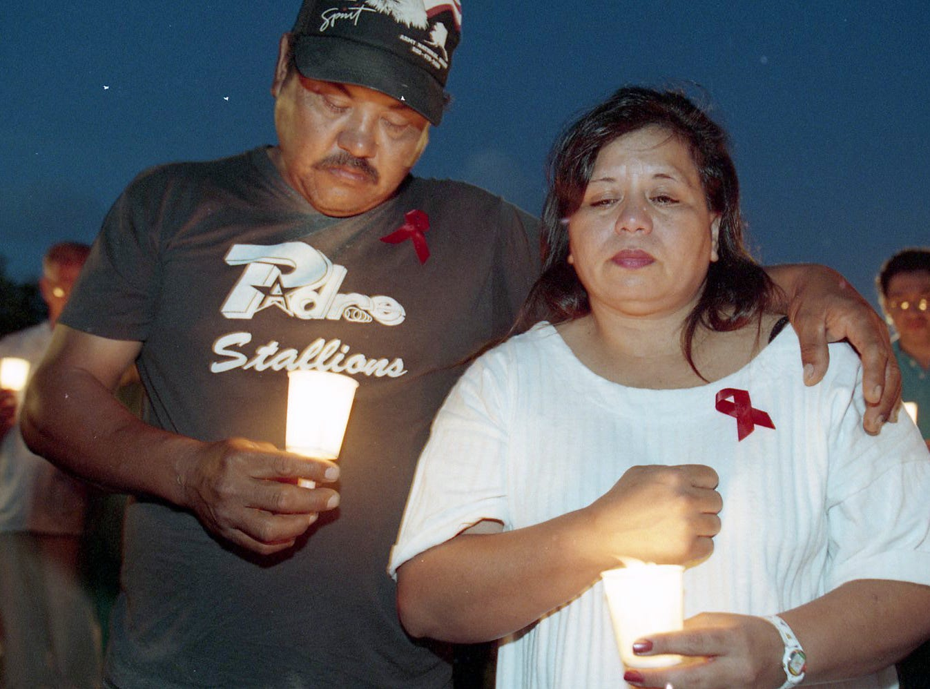 Joe and Diane Carrizales pause during the reading of a list of loved ones lost to AIDS at the 12th international AIDS Candlelight Memorial and Mobilization on May 21, 1995 at Heritage Park. The Carrizales had lost their son Joe Anthony to AIDS almost a year and a half prior.