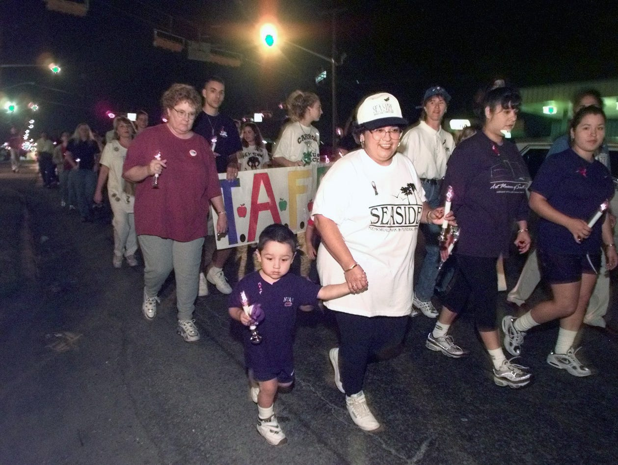 Norma Linda Garcia walks with her grandson Rammi Garcia, 3,  for the second year together during the Eighth Annual Candle Light Procession.  Mrs. Garcia lost a friend to AIDS in August of this year.  Photo/David Pellerin 12-1-98