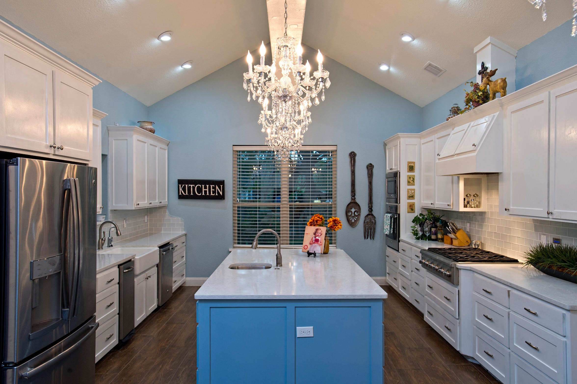 The most complimented area of the home is the kitchen which is finished in pleasant colors with unique lighting from crystal chandeliers.   The area features a cathedral ceiling,  great storage, an island with a 2nd sink plus a commercial style gas cook top.