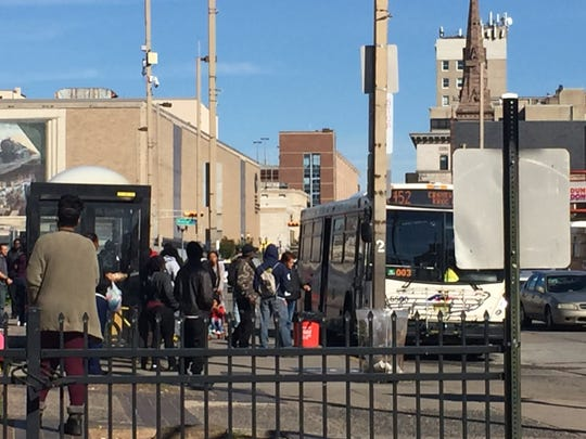 Passengers board a bus Friday morning at the Walter Rand Transportation Center in downtown Camden, where a city man allegedly recruited two men for bank robberies.