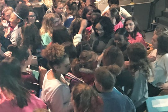 Model Melissa Roshan, center, is swarmed by Chillicothe Middle School students following her presentation on making choices Thursday morning.