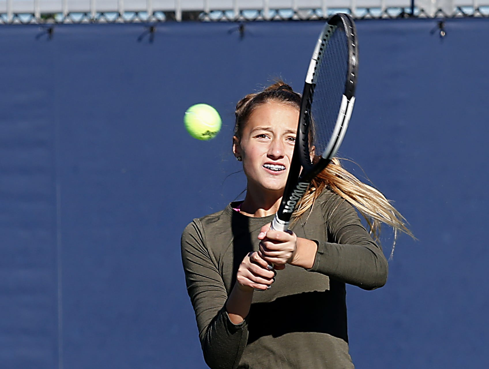 Ursuline's Bridget Estes returns a volley during the Division I doubles bracket at the Lindner Family Tennis Center in Mason Friday, Oct. 19, 2018.