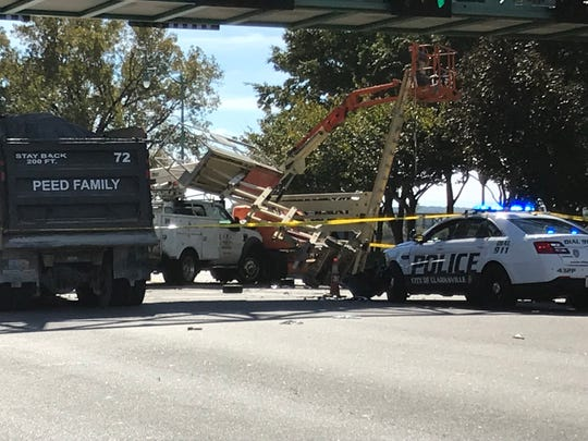 Four vehicles, including a stationary police car, two lifts being used to paint a pedestrian overpass and a utility vehicle were involved in a Friday crash that injured five.