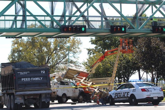 Five people were injured after police say a utility truck failed to maintain a lane shift where work was being done on a pedestrian overpass, struck a stationary CPD cruiser and then both lifts which each had two people on them Friday, Oct. 19, 2018, on Riverside Drive in Clarksville.