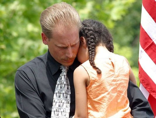Clarksville Police Detective Tim Anderson holds one of Officer David Scott's young daughters during a 2003 memorial service marking the one year anniversary of her father's death alongside Officer Yamil Baez-Santiago. The man who caused the officers' death attended a parole hearing Thursday, but only one seven board members have cast votes.
