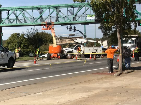 The wreck that shut down Riverside Drive involved a utility truck that hit stationary police car and two lifts being used to repaint a pedestrian overpass on Friday, injuring five people and disrupting traffic.