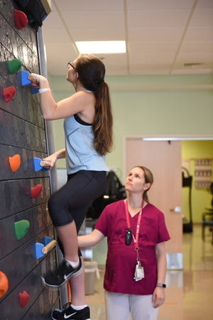 Patient, Rebecca Farrell, uses the climbing wall at Children's Specialized Hospital as part of her physical therapy for chronic pain management. Physiatrists also use this wall for therapy of children with cerebral palsy.