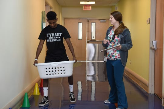 Patient, Elias Smith, practices carrying a laundry basket as part of his occupational therapy at Children's Specialized Hospital. Practicing this everyday activity prepares patients in the Chronic Pain Management Program for discharge and life at home.