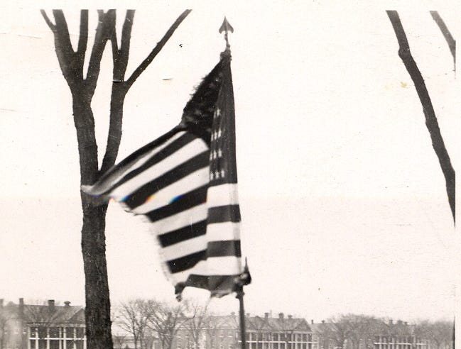 Women carry a flag at Fort Des Moines.