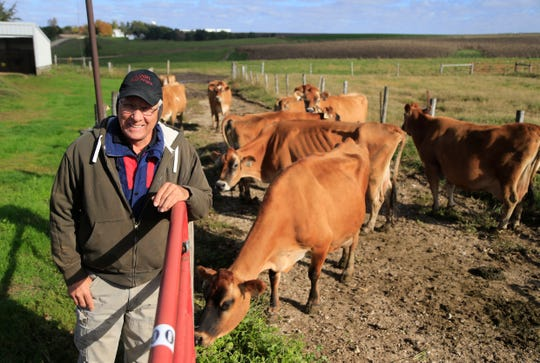 Eric Lyon stands next to a few remaining dairy cows on his Toledo farm last month. His family is moving out of the dairy business after 95 years and starting fresh with beef cattle amid a downturn in the U.S. dairy industry.