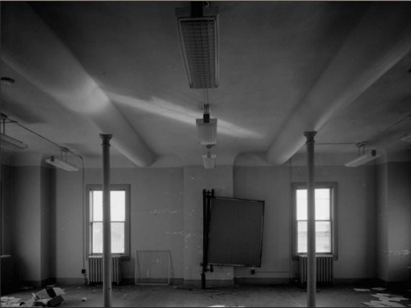 Interior of the Fort Des Moines barracks showing the historic columns and cove plaster ceilings.
