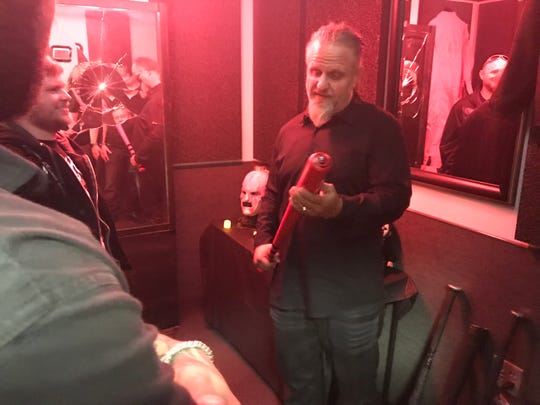 Slipknot co-founding member M. Shawn Crahan shows fans band memorbia at Guitar Center in Clive, Iowa on Oct. 18, 2018.