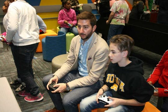 Kum & Go President Tanner Krause plays a video game with a Boys and Girls Clubs of Central Iowa club member. Krause is a Boys and Girls Clubs board member.
