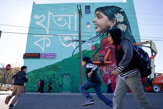 "Students run past a mural being painted by Artist Victor ""MARKA27"" Quinonez as part of the A OneHamtramck Mural Project titled ""Bangladesh : Coming to America."""
