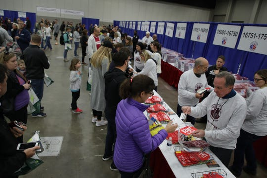 Runners get their bibs for the 2018 Detroit Free Press/ Chemical Bank Marathon during the Metro Detroit Chevy Dealers Health & Fitness Expo at Cobo Center in Detroit on Friday, Oct. 19, 2018.