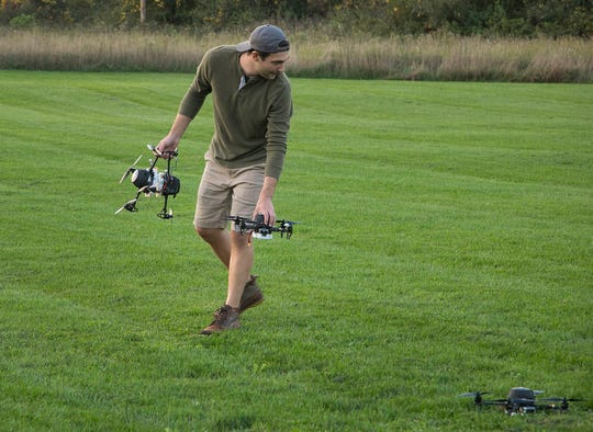 Firefly Drone Shows Ryan Sigmon, 28, of West Bloomfield helps to position 60 drones in a field near Holly on Tuesday, Oct. 9, 2018 to test for a upcoming show.