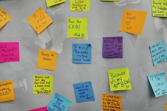 People write down why they run after getting their bibs for the 2018 Detroit Free Press/ Chemical Bank Marathon during the Metro Detroit Chevy Dealers Health & Fitness Expo at Cobo Center in Detroit on Friday, Oct. 19, 2018.