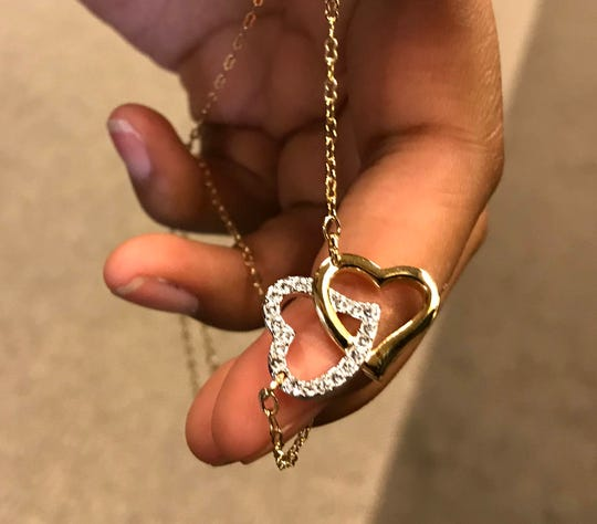 C'Nai Lange, 17, of Macomb Township holds a double heart necklace that she bought for her mom, Kathy Lange. She gave her mom the necklace during the adoption proceeding in Macomb County Circuit Court on Oct. 19, 2018.