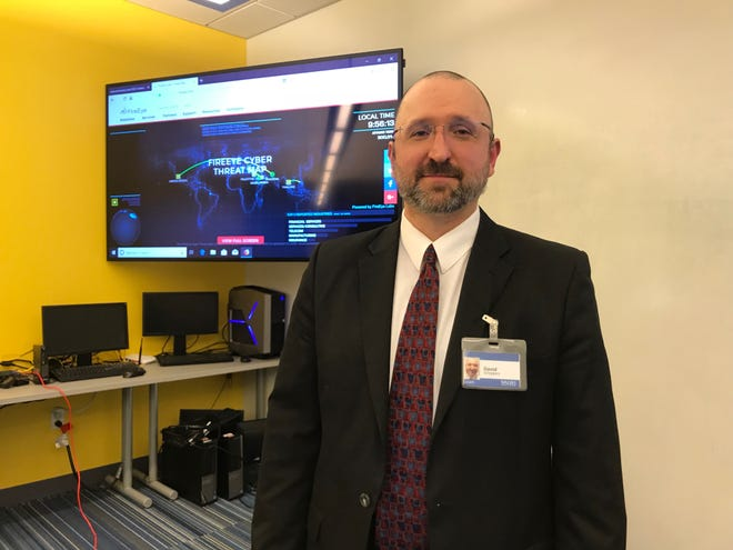 Dave Schippers, a local cybersecurity expert and assistant professor at Walsh College, standing at the school's CyberLab. On Oct. 19, 2018, Schippers spoke to students from Henry Ford II High School about what a career in cybersecurity may look like.