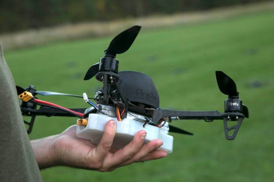 Firefly Drone Shows Ryan Sigmon, 28, of West Bloomfield holds one of the 60 proprietary drones before it is launched in a field near Holly on Tuesday, Oct. 9, 2018 to test for a upcoming show.
