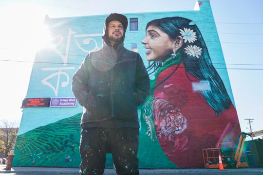 "Artist Victor ""MARKA27"" Quinonez poses for a photo with the biggest public mural in America on Bangladeshi life, that he is painting on the side of Bridge Academy West in Hamtramck."