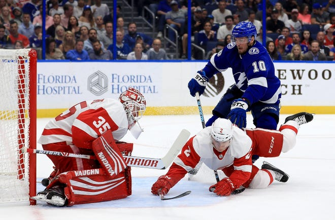 Red Wings goalie Jimmy Howard, left, and Joe Hicketts stop a shot from Lightning's J.T. Miller during Thursday's 3-1 loss in Tampa.