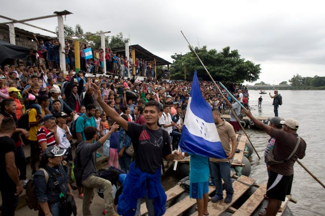 Hundreds of Honduran migrants stand at the shore of the Suchiate river on the border between Guatemala and Mexico, in Tecun Uman, Guatemala, Thursday, Oct. 18, 2018.