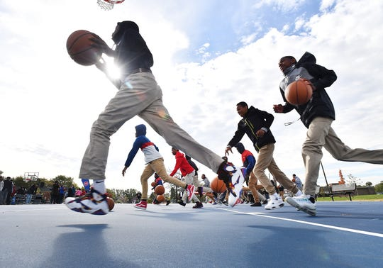 Boys and girls from Northwestern High School try out the new court during a clinic that followed the press conference.