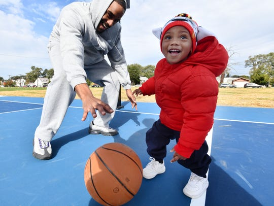 Jeffery Wilson and son Jace Wilson, 1,  try out the new basketball court at Littlefield Park in Detroit, one of 60 basketball courts that will be renovated by the Detroit Pistons by 2023.  Detroit Pistons vice chairman Arn Tellem, Detroit Mayor Mike Duggan and others unveil the first of 60 renovated basketball courts in 50 city parks in Detroit, Michigan on October 19, 2018.  (Image by Daniel Mears / The Detroit News)