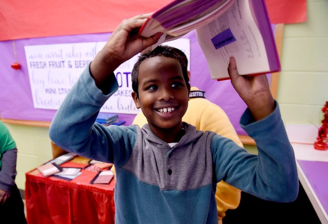 Fifth-grader Abdullahi Ibrahin, 10, finds the clue for the idiom inside a cut-out section of a book during his team search at Owen Intermediate School in Belleville.