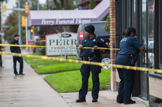 "Detroit Police officers use crime scene tape to cordon off the area while they execute a search warrant at Perry Funeral Home in Detroit Friday afternoon, October 19, 2018. Detroit Police Chief James Craig said, ""We're looking for evidence of improper disposal of remains or any other improprieties."""